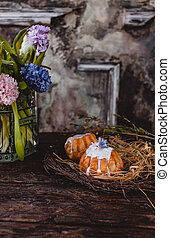 Easter cakes in nest with spring flowers in jug on table