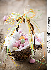 Easter candy - Colorful easter candy in brown basket with...