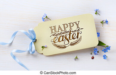 Easter card and spring flowers on wood background