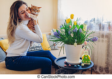 Easter celebration at home. Woman hugs cat relaxing on couch. Spring flowers in pot decorated with eggs and bunny.