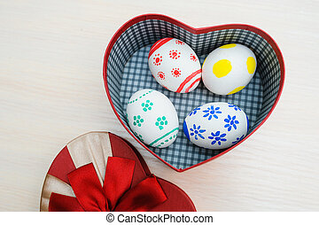 Easter colored eggs in a box in the shape of heart