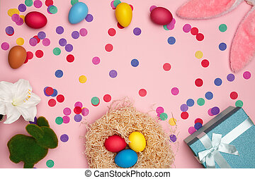 Easter composition eggs bunny confetti box with gift on a pink background. Flat lay, top view, copy space