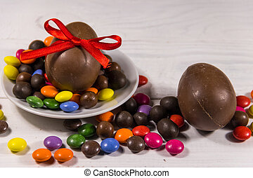 Easter composition with chocolate eggs on white wooden background
