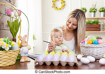 Easter concept. Happy mother and her cute child getting ready for Easter