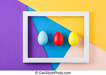 Easter concept. wooden frame with easter eggs on colorful background