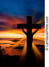 A cross at sundown on the ocean