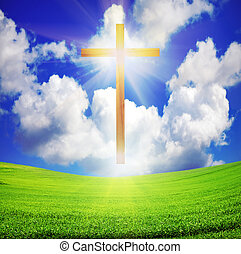 easter cross over green field and blue sky
