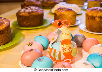 Easter cuisine. Close-up plate with colored eggs on yellow tablecloth on background of Easter cakes.