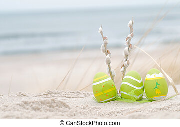 Easter decorated eggs and catkin on sand. Beach and ocean in the background