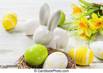 Easter decoration on a white wooden background with daffodils