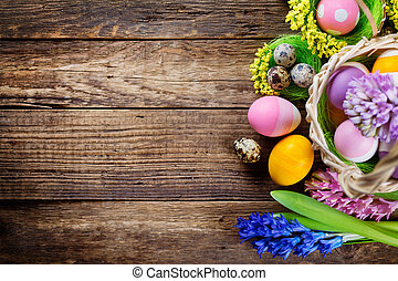 Easter decorations on wooden table, colored eggs and flowers...