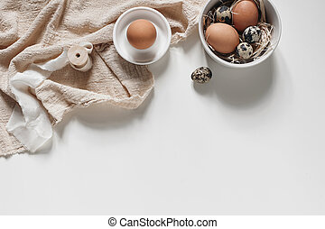 Easter decorative frame, banner. Spring still life with natural quail and hen eggs, ceramic bowls and linen napkins isolated on white table background. Neutral feminine styled stock photo, top view.