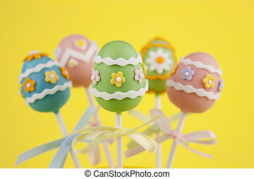 Easter egg cake pops on yellow background