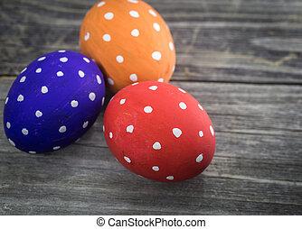Easter egg colored polka dots lie on wooden background