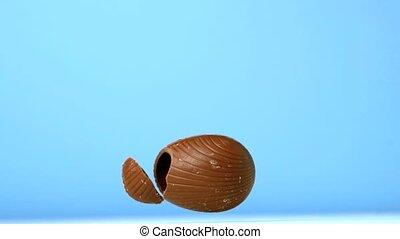 Easter egg falling against blue background in slow motion