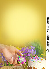 Easter egg in a hand on a background of Easter decoration and spring flowers. Easter breakfast concept.