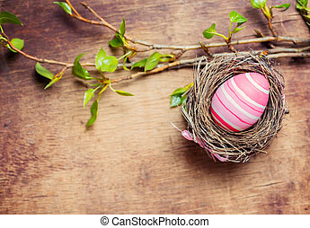 Easter egg in nest on wooden background. Top view