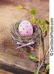 Easter egg in nest on wooden background.