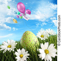 Easter egg in the grass with daisies