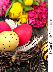 Easter egg nest with flowers on rustic wooden background