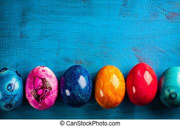 Easter egg on blue wooden background.