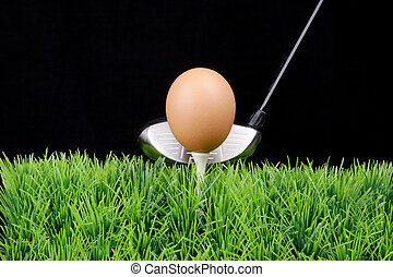 Easter egg on golf tee with golf driver