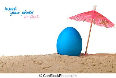 Easter egg on the beach under an umbrella