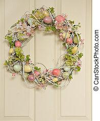 Easter egg wreath on a wooden door.