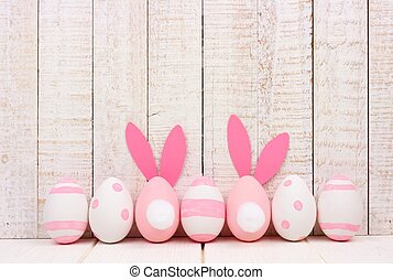 Easter eggs against white wood, two with bunny tails and ears