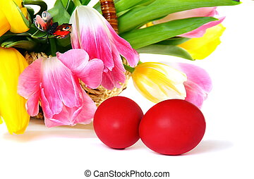 Easter eggs and a basket with colorful tulips.