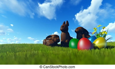 Easter Eggs and Chocolate Bunnies on green meadow against blue sky