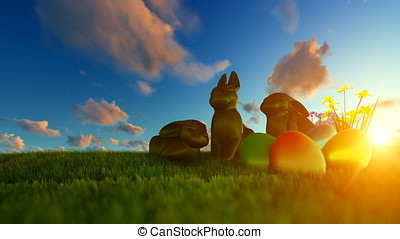 Easter Eggs and Chocolate Bunnies on green meadow against beautiful sunrise