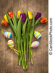 Easter eggs and colorful tulips bouquet