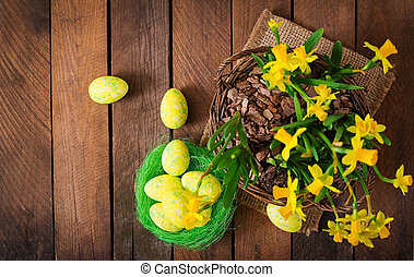 Easter eggs and flowers on a dark wooden background. Top view