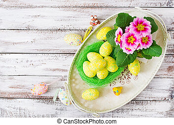 Easter eggs and flowers on a light wooden background. Top view