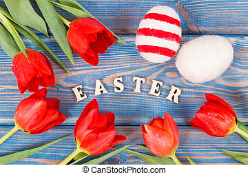 Easter eggs and fresh red tulips on boards, festive decoration