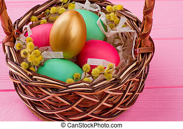 Easter eggs and pussy-willow in woven basket.