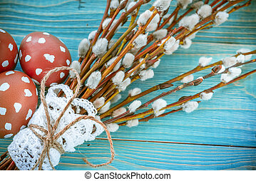 Easter eggs and willow branches on a wooden background