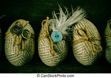 Easter eggs covered with scraps of newspaper wrapped in a jute twine with glued buttons. Handmade easter egg decoration.