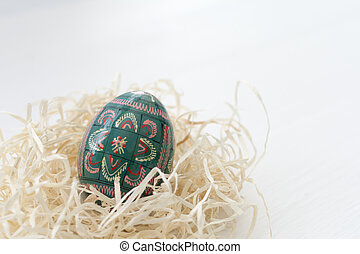 Easter eggs decoration in hay nest on white wooden background.