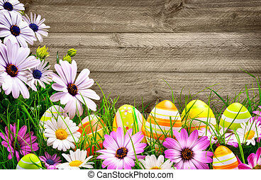 Easter eggs, flowers and wooden background