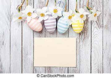 Easter eggs, fresh spring daffodils on white wooden background. Easter card.