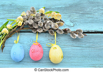 Easter eggs hanging on ribbons and pussy-willow at a blue...