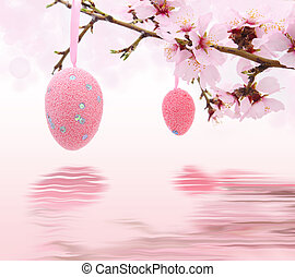 Easter eggs hanging on the almond tree reflected in water