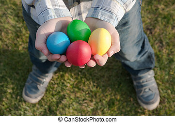 Easter eggs hunt - child holding four colored Easter eggs