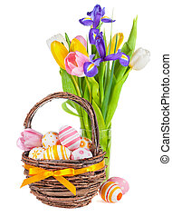 Easter eggs in a basket and spring flowers