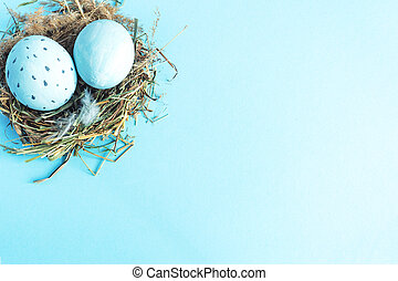 Easter eggs in a nest of grass. Blue background. Copy space