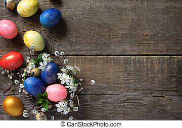 Easter eggs in a nest with willow branches and spring flowers on a gray wooden background. Top view flat lay background. Copy space.