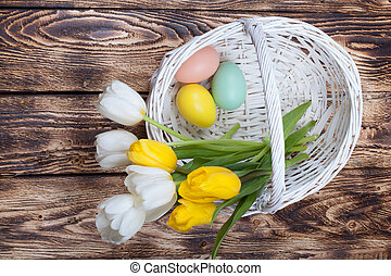 Easter Eggs in a white basket with tulips