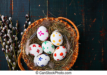 Easter eggs in a wicker basket on wooden table